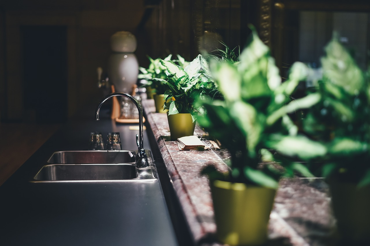 Jak dopasować meble do wnętrza – biała kuchnia drewniana podłoga.